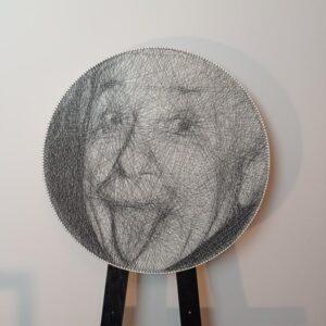 Portret Alberta Einsteina wykonany techniką string art. Praca jest zaprezentowana na sztaludze.