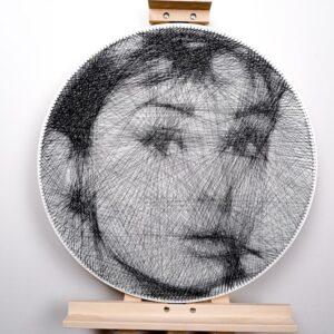 Portret Audrey Hepburn wykonany techniką string art. Praca jest zaprezentowana na sztaludze.