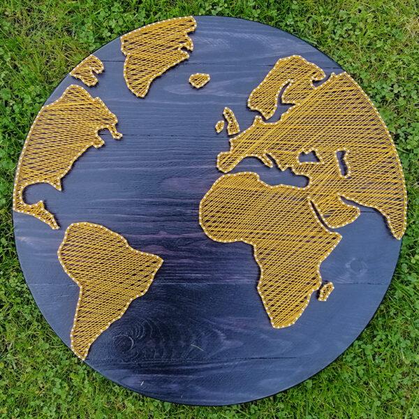 Stringartowa mapa świata. Kontynenty wypleciono z żółtych nici. Praca jest wykonana na okrągłej desce w kolorze niebieskim.
