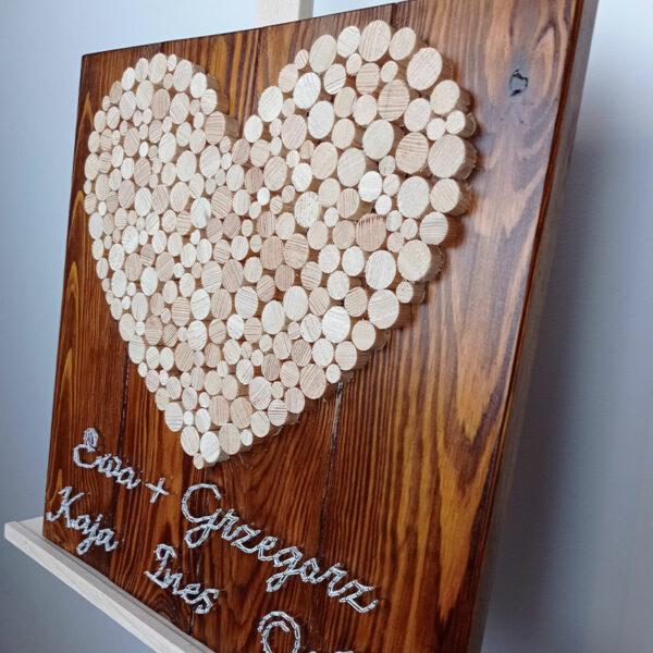 """Obraz stringartowy """"Jubileusz"""": drewniane okrągłe elementy tworzą kształt serca, a na dole pracy znajdują się wyplecione z nici imiona. Zdjęcie w zbliżeniu, z ukosa."""