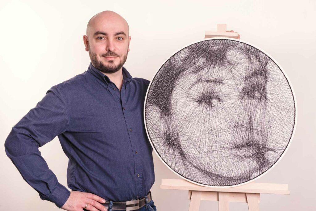 Portret Audrey Hepburn wykonany techniką string art. Praca jest zaprezentowana na sztaludze, obok której stoi autor.