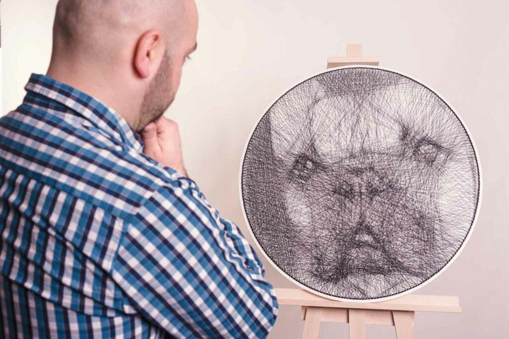 Portret wykonany techniką string art. Plątanina czarnych nici tworzy pyszczek buldoga francuskiego. Na zdjęciu widać też autora wpatrzonego w obraz.