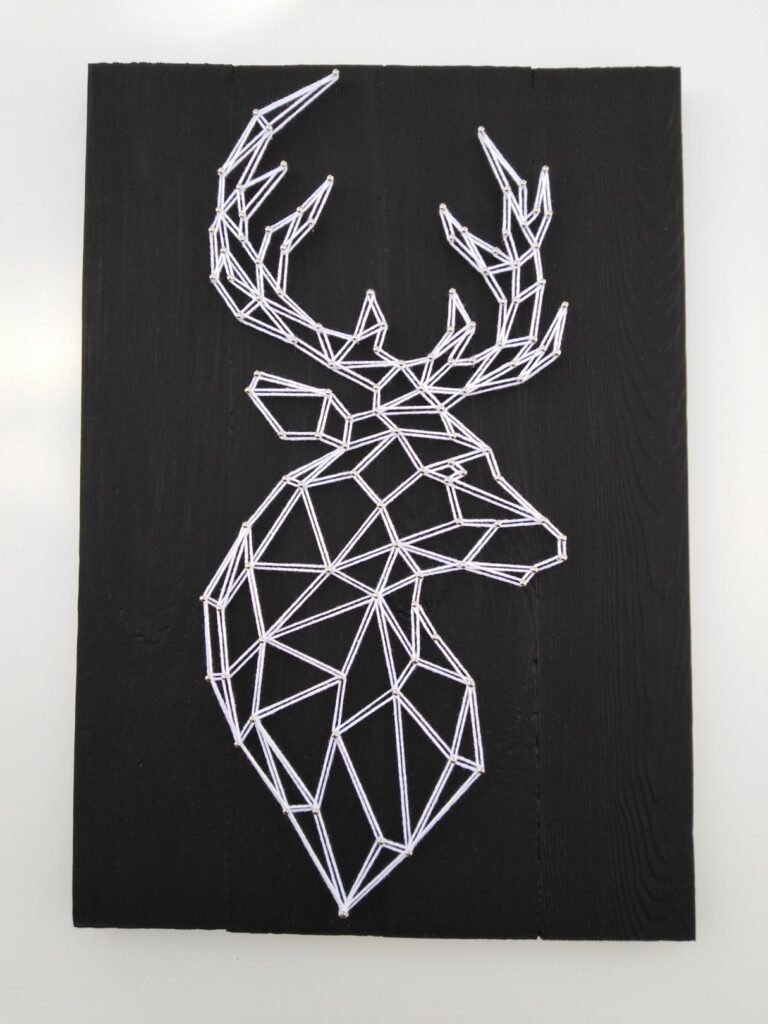 String art przedstawiający jelenia z bujnym porożem, którego głowa skierowana jest w prawo. Do wykonania pracy użyto białych nici kontrastujących z ciemną deską.
