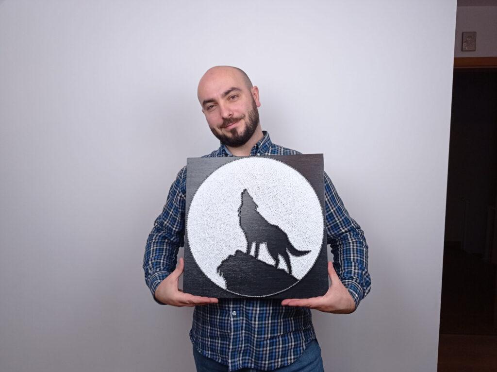 String art przedstawiający wyjącego wilka stojącego na skale. Zwierzę jest umieszczone na okrągłym, białym tle utworzonym z nici.