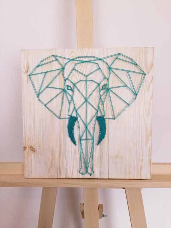Obraz String Art przedstawiający głowę słonia, do wyplatania użyto turkusowych nici, podstawę obrazu stanowią jasne deski.