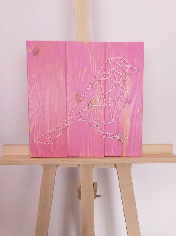 Obraz String Art przedstawiający ptaka, ma kształt kwadratu, a deski są w kolorze różowym z delikatnymi, jasnymi refleksami oddającymi słoje drewna.