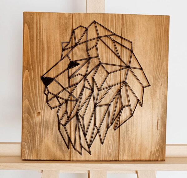 Obraz String Art przedstawiający zwierzęcego patronusa – lwa. Do wyplatania użyto ciemnych nici i jasnych desek.
