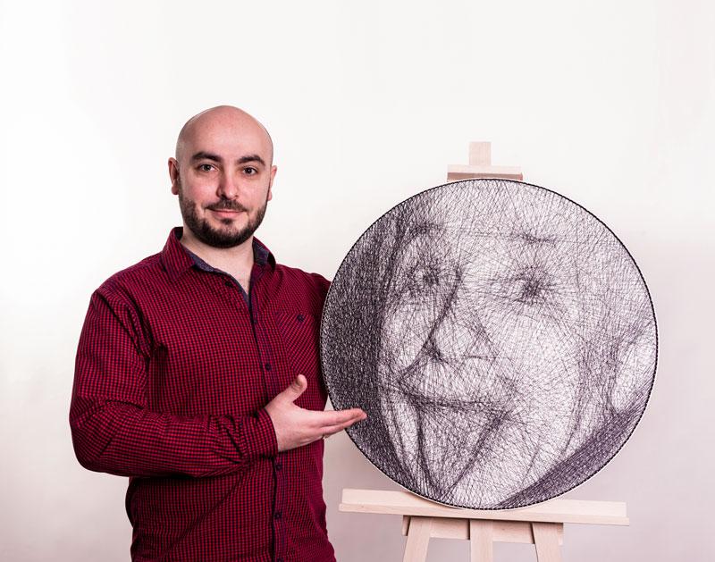 Portret Alberta Einsteina wykonany techniką string art. Praca jest zaprezentowana na sztaludze, obok której stoi autor.
