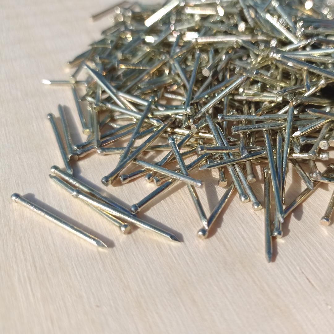 Obraz przedstawiający rozsypane gwoździe, które są najlepsze w technice string art